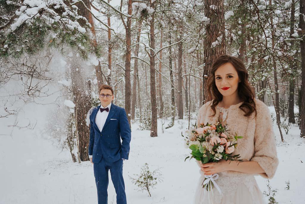 spadający śnieg z drzewa na pana młodego zimowa sesja Piotr czyżewski fotografia