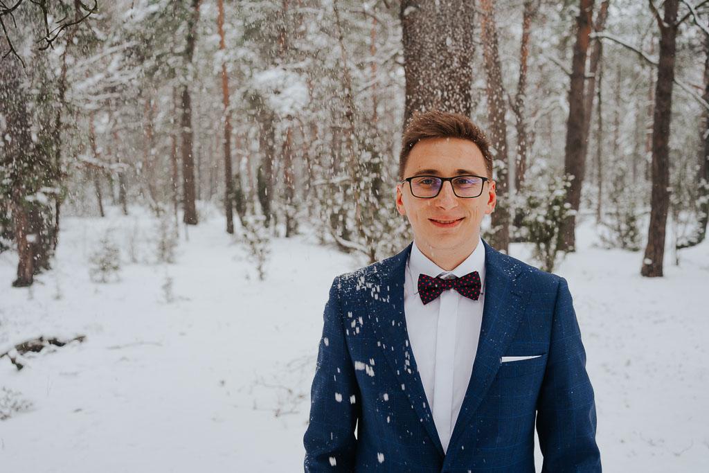 spadający śnieg na pana młodego, portret pana młodego w lesie zimą zimowa sesja Piotr czyżewski fotografia