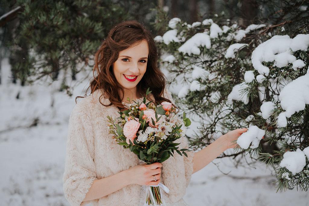 portret panny młodej w lesie zimą, czerwone usta panny młodej suknia ślubna z futerkiem zimowa sesja Piotr czyżewski fotografia