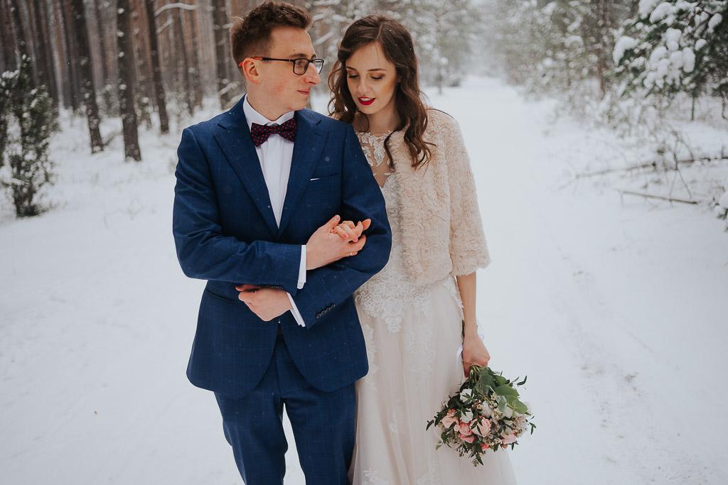 para młoda spaceruje w lesie zimą zimowa sesja Piotr czyżewski fotografia