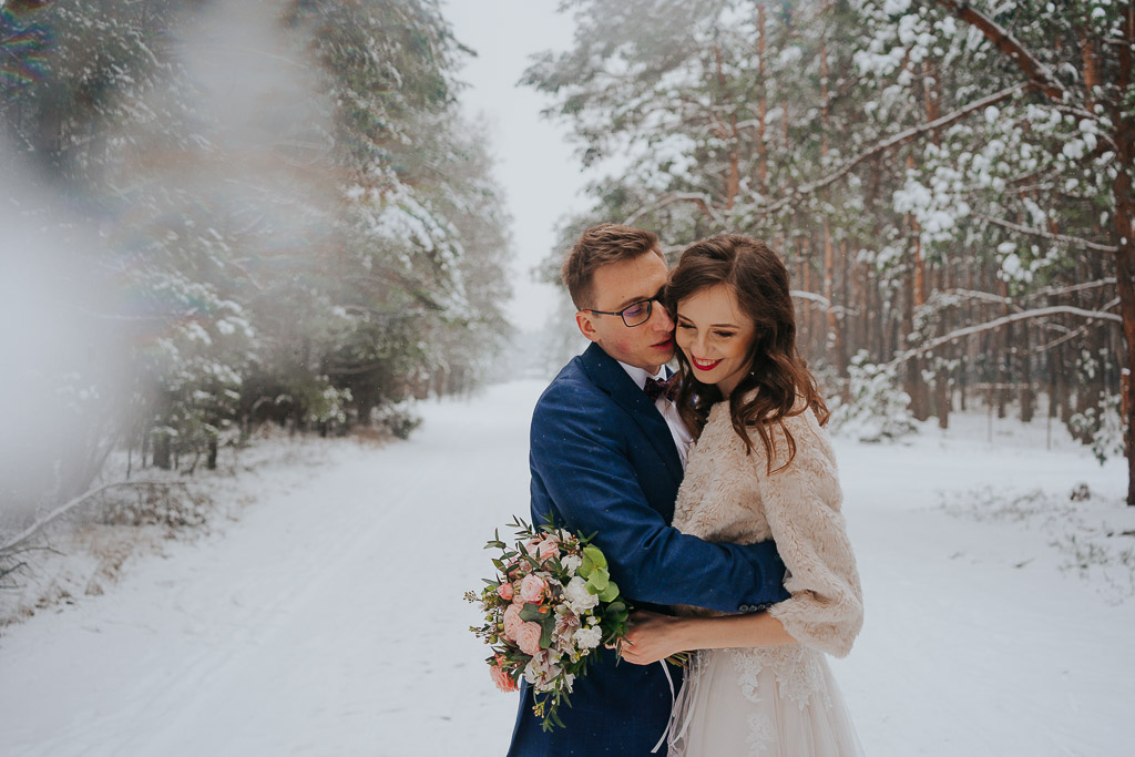 suknia ślubna, futerko do sukni ślubnej, przytulona w lesie para młoda zimowa sesja Piotr czyżewski fotografia