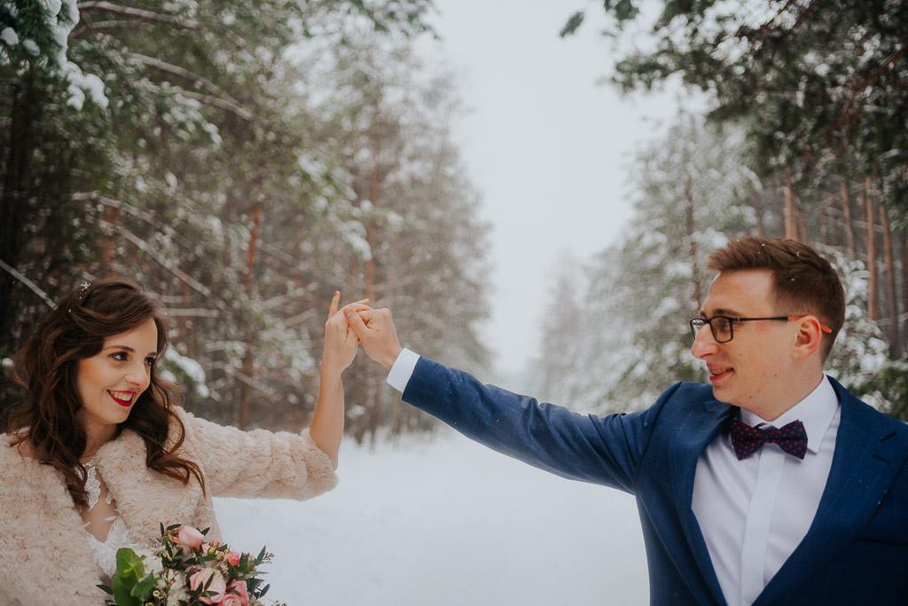 para młoda trzyma się za ręce czerwone usta panny młodej zimowa sesja Piotr czyżewski fotografia