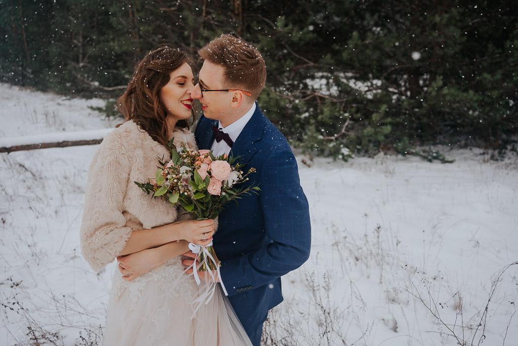 pocałunek pary młodej w lesie zimą zimowa sesja Piotr czyżewski fotografia