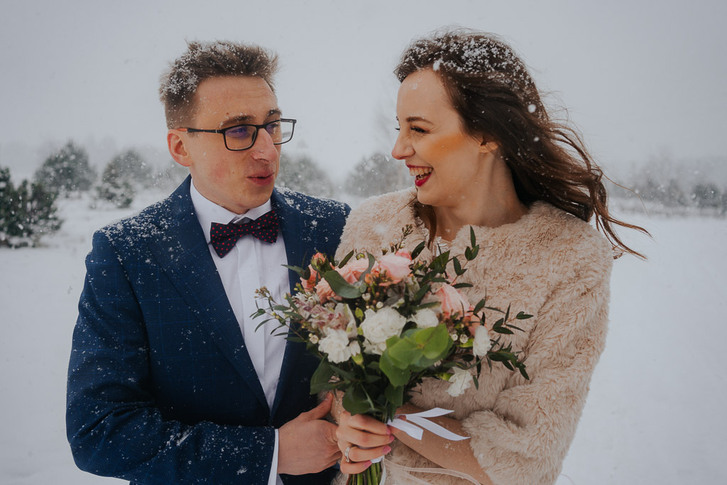 uśmiechnięta para młoda zimą w śniegu zimowa sesja Piotr czyżewski fotografia