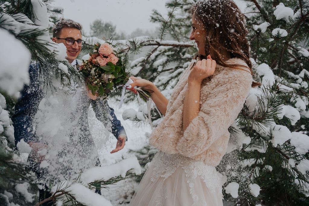 roześmiana para młoda w zaśnieżonych drzewach zimowa sesja Piotr czyżewski fotografia