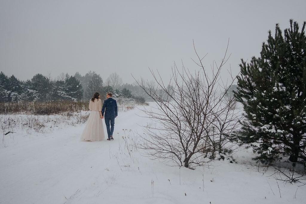 para młoda spaceruje po śniegu zimowa sesja Piotr czyżewski fotografia