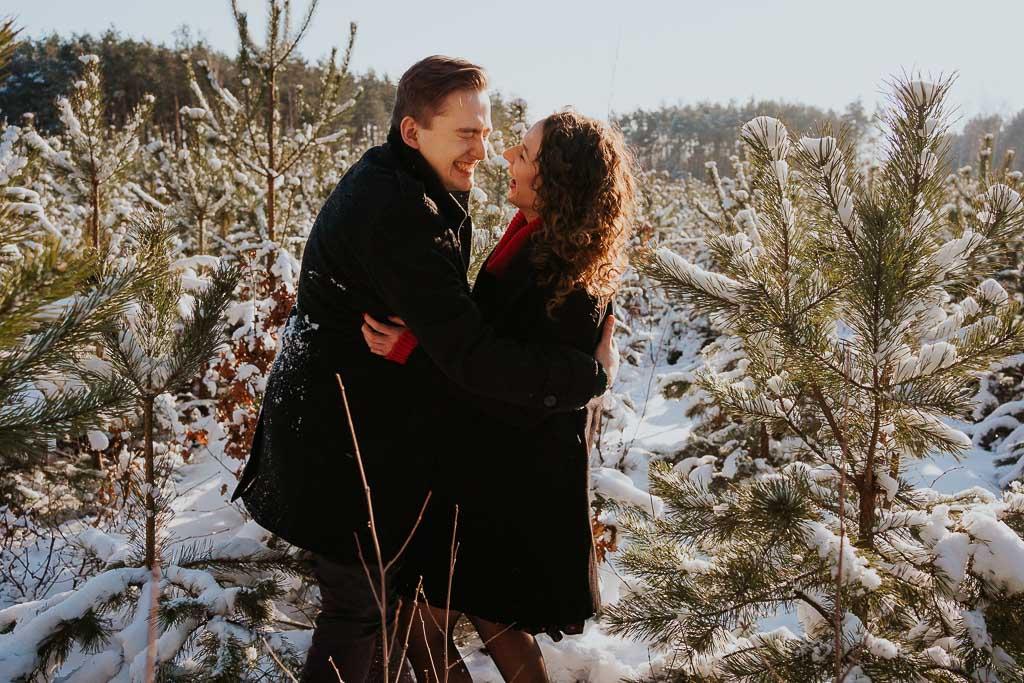 uśmiechnięta para w lesie podczas sesji, sesja narzeczeńska zimą fotograf Legionowo Piotr Czyżewski