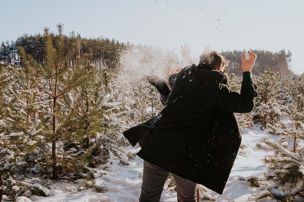 zakochana para rzuca w siebie śniegiem sesja narzeczeńska zimą fotograf Legionowo Piotr Czyżewski