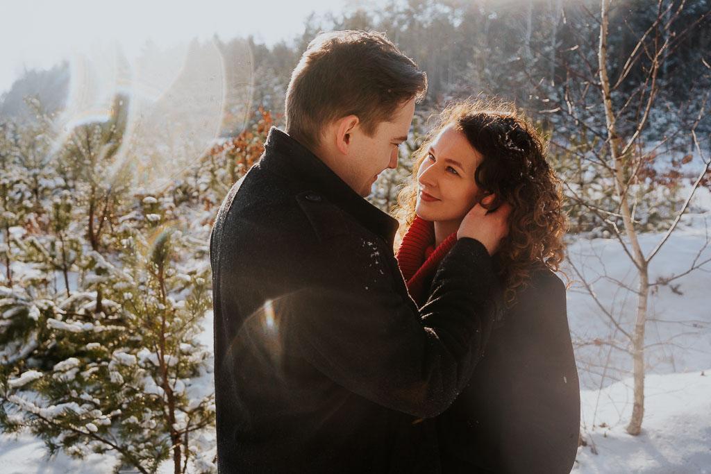 zapatrzona w siebie para w lesie zimą sesja narzeczeńska zimą fotograf Legionowo Piotr Czyżewski