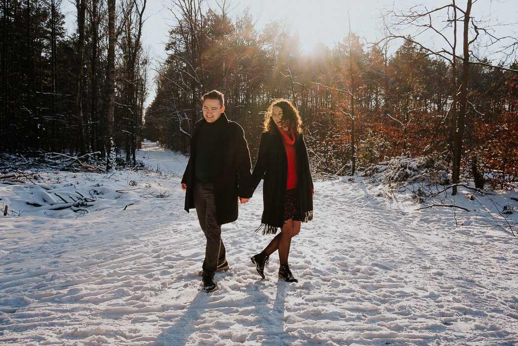 szczęśliwa para spaceruje zimą w lesie po sniegu fotograf Legionowo Piotr Czyżewski
