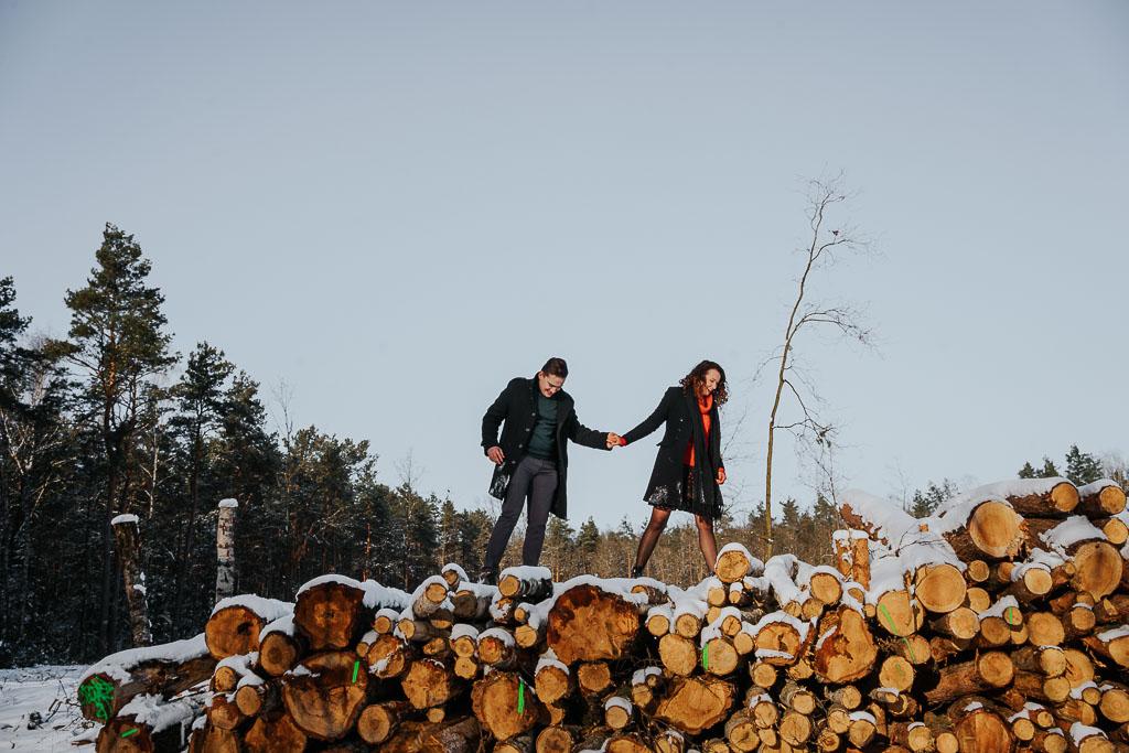 zakochani idą po ściętym drewnie zima fotograf Legionowo Piotr Czyżewski