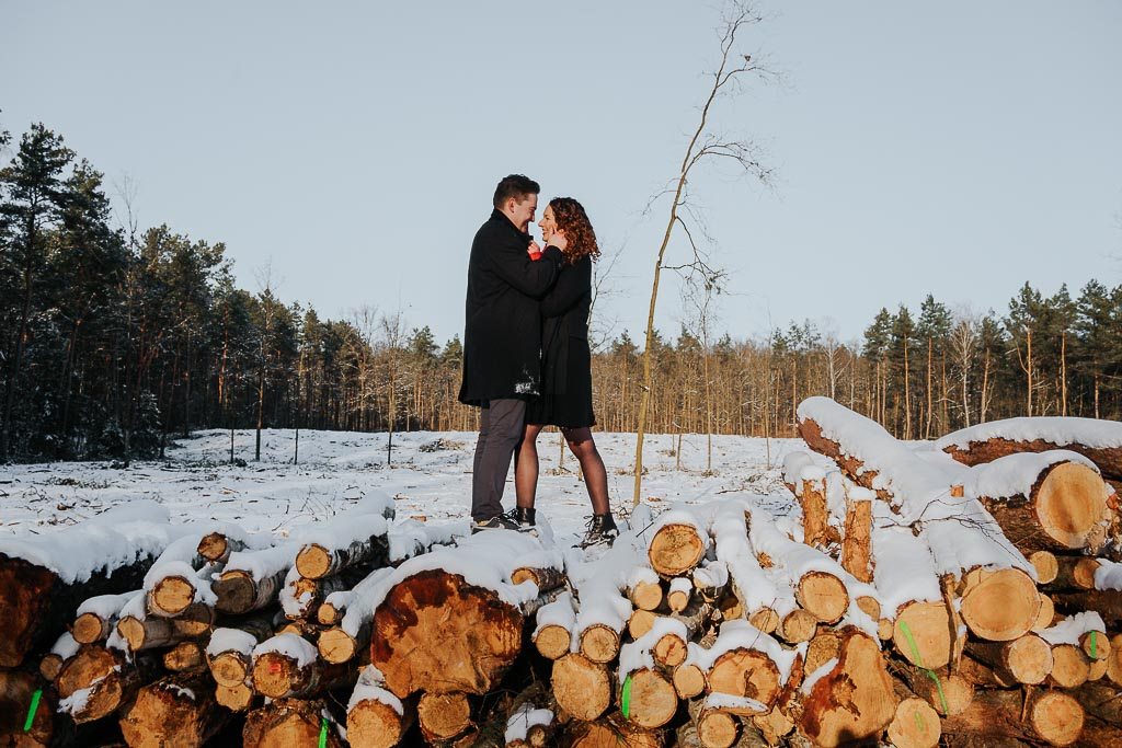 zakochani na pniach drewna sesja narzeczeńska zimą sesja narzeczeńska zimą fotograf Legionowo Piotr Czyżewski