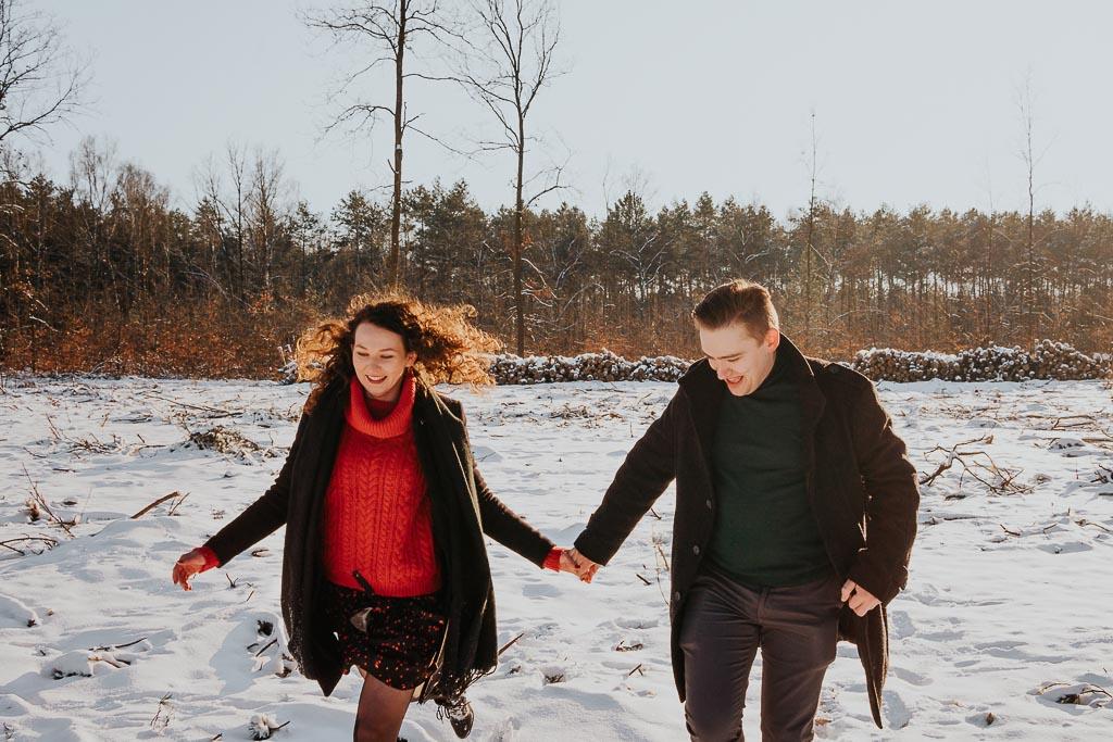 radosna para spaceruje po śniegu w promieniach słońca sesja narzeczeńska zimą fotograf Legionowo Piotr Czyżewski