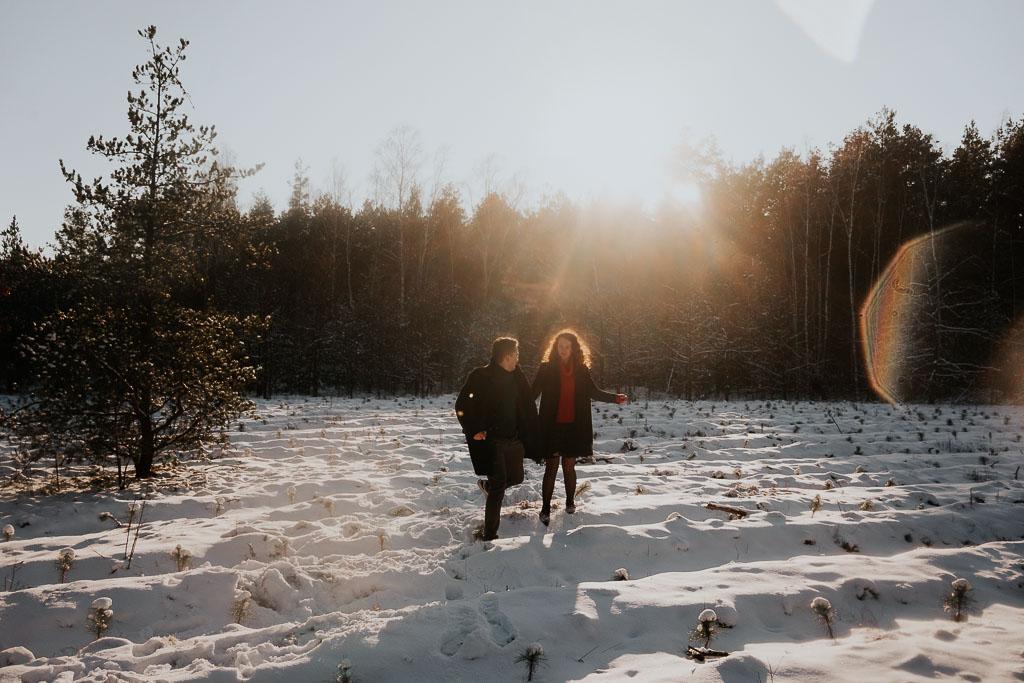 promienie słońca zachodzą za las sesja narzeczeńska zimą fotograf Legionowo Piotr Czyżewski