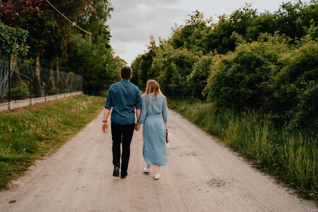 para trzyma się za ręce podczas spaceru nad jeziorem sesja nad jeziorem Piotr Czyżewski fotograf Legionowo