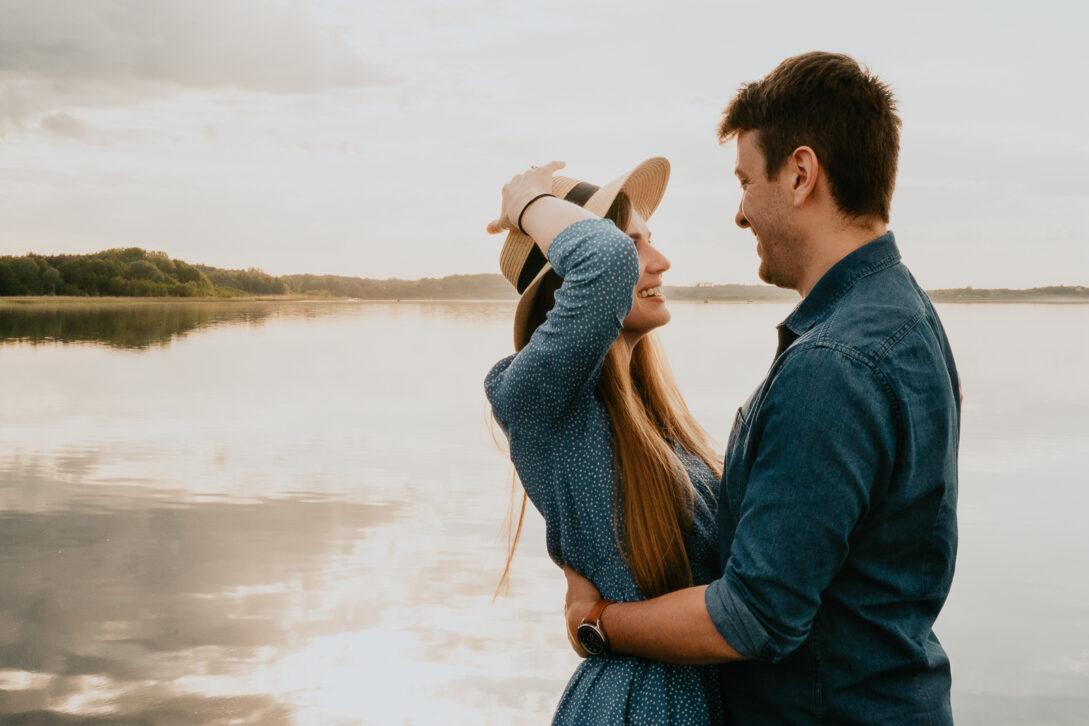 dziewczyna przytula chłopaka trzyma ręką na głowie kapelusz sesja nad jeziorem Piotr Czyżewski fotograf Legionowo