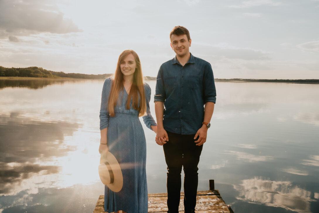 portret zakochanej pary na drewnianym pomoście para trzyma się za ręce sesja nad jeziorem Piotr Czyżewski fotograf Legionowo