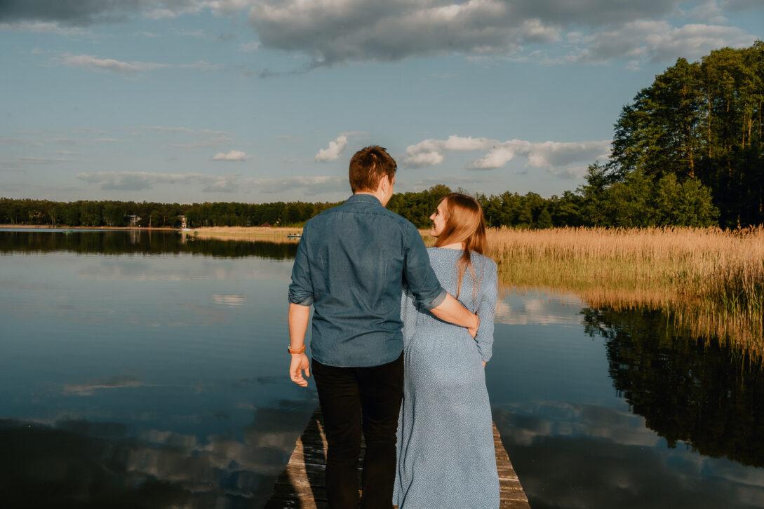 przytulona para schodzi z pomostu sesja nad jeziorem Piotr Czyżewski fotograf Legionowo