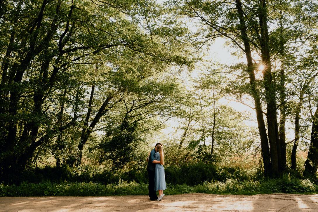 dziewczyna stoi na palcach przytula chłopaka w lesie sesja nad jeziorem Piotr Czyżewski fotograf Legionowo