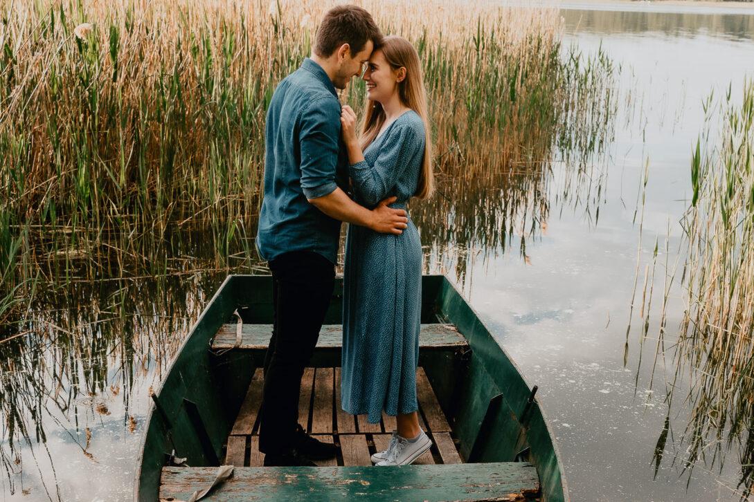 para stoi na łódce i przytula się do siebie sesja nad jeziorem Piotr Czyżewski fotograf Legionowo