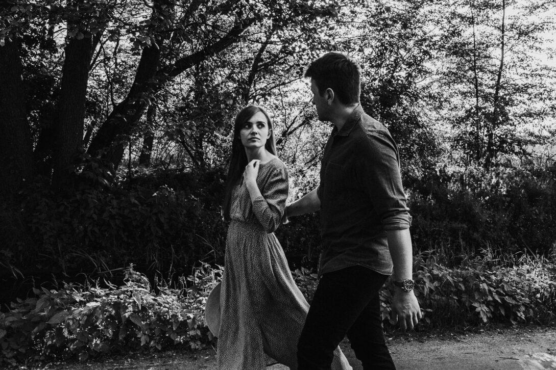 para spaceruje w lesie, ona patrzy na niego sesja nad jeziorem Piotr Czyżewski fotograf Legionowo