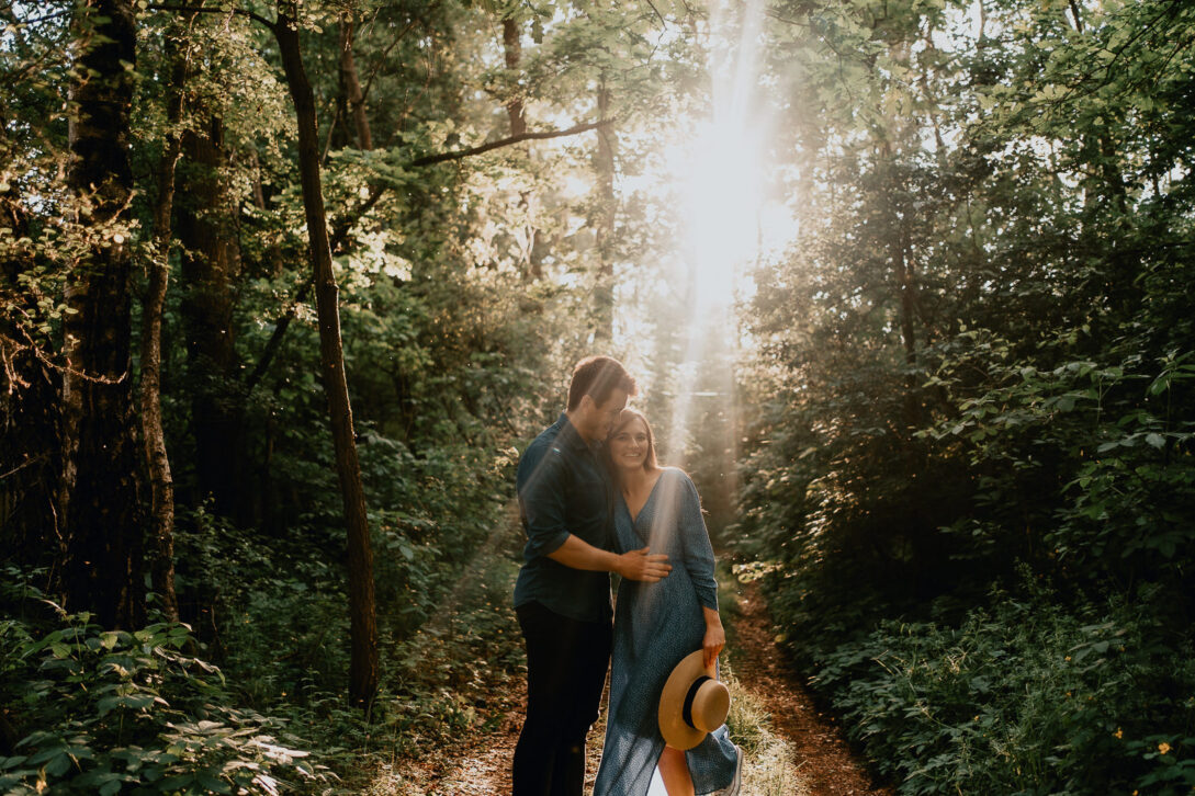 przytulona para w promieniach słońca w lesie sesja nad jeziorem Piotr Czyżewski fotograf Legionowo