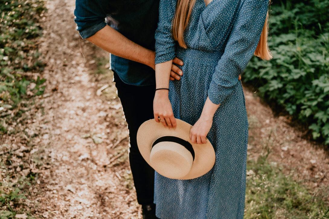 ręce chłopaka przytulają dziewczynę kapelusz w rękach dziewczyny sesja nad jeziorem Piotr Czyżewski fotograf Legionowo