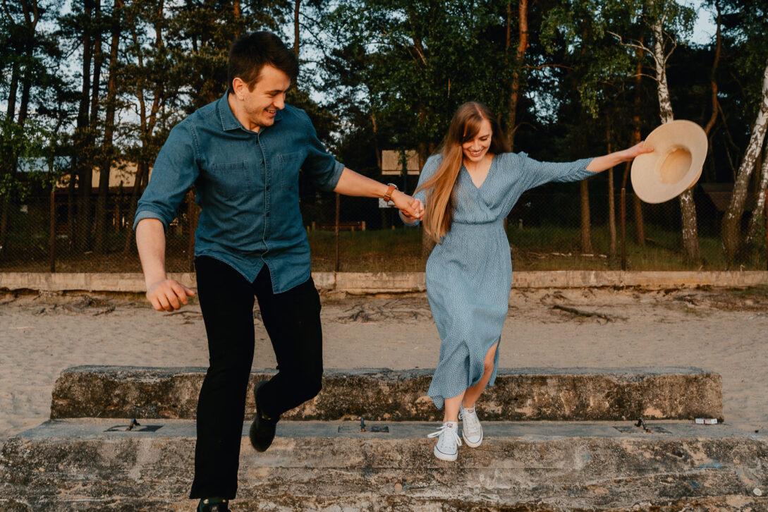 para skacze z betonowych schodów trzymając się za ręce sesja nad jeziorem Piotr Czyżewski fotograf Legionowo