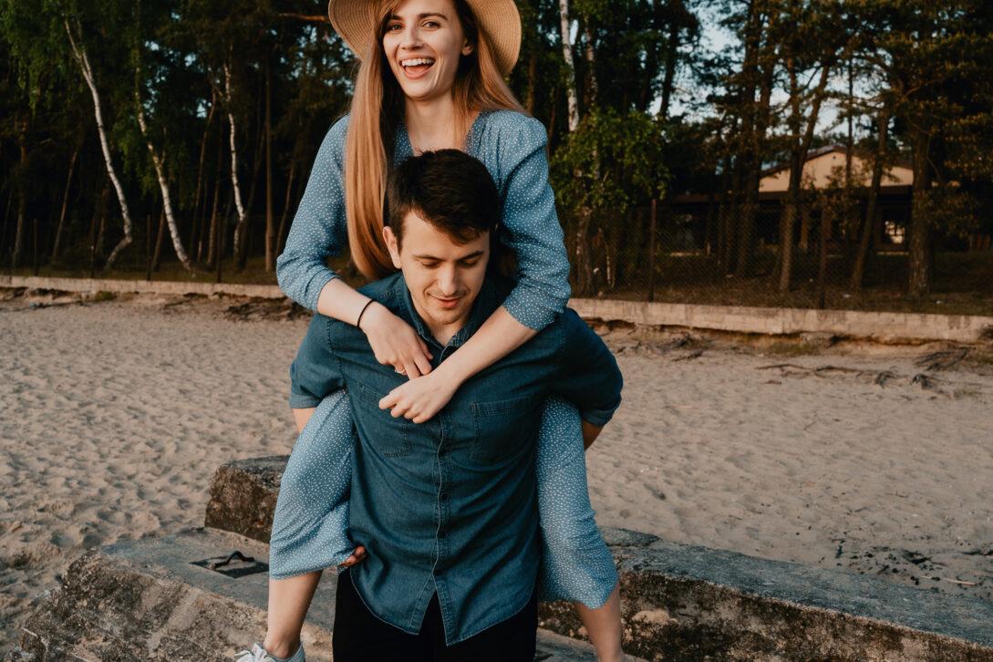 chłopak niesie na barana dziewczynę sesja nad jeziorem Piotr Czyżewski fotograf Legionowo