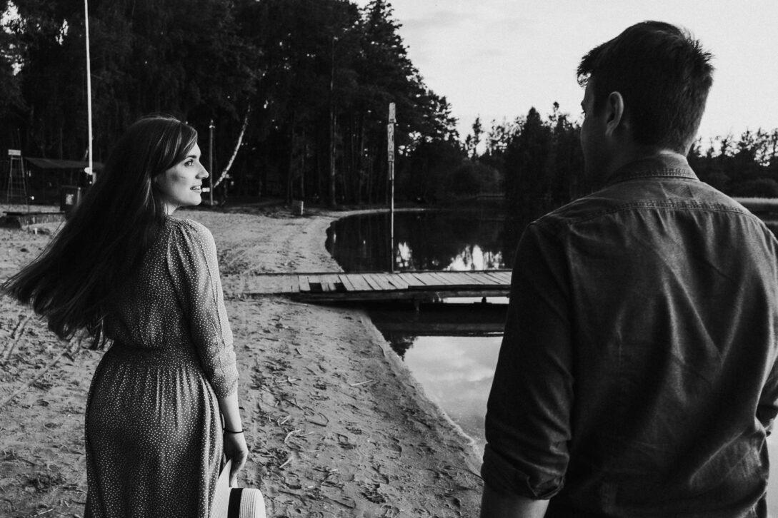 para spaceruje nad jeziorem dziewczyna ogląda się za siebie sesja nad jeziorem Piotr Czyżewski fotograf Legionowo