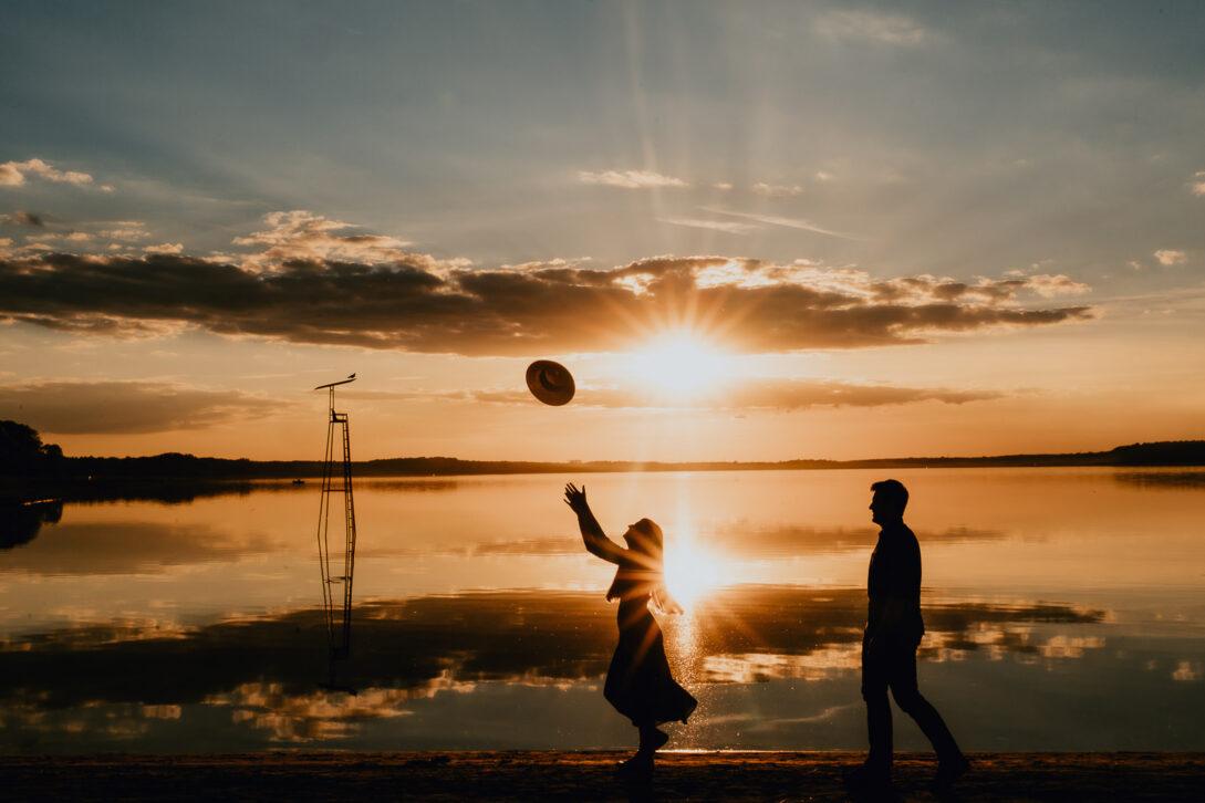 para idzie brzegiem jeziora o zachodzie słońca dziewczyna podrzuca kapelusz sesja nad jeziorem Piotr Czyżewski fotograf Legionowo