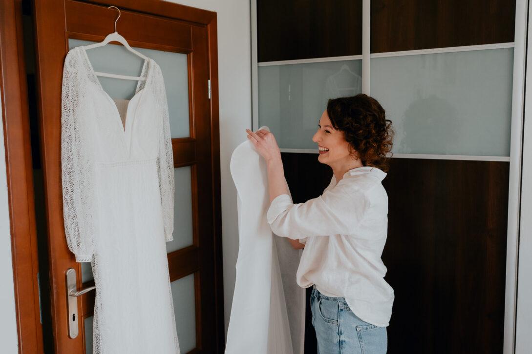 panna młoda wiesza suknie na drzwiach wesele w namiocie piotr Czyżewski fotograf na ślub Legionowo