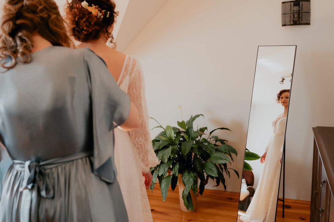 panna młoda podczas przygotowań zerka w lustro wesele w namiocie piotr Czyżewski fotograf na ślub Legionowo