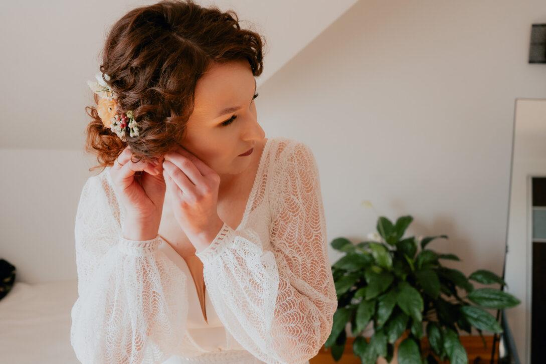 panna młoda zapina kolczyki wesele w namiocie piotr Czyżewski fotograf na ślub Legionowo