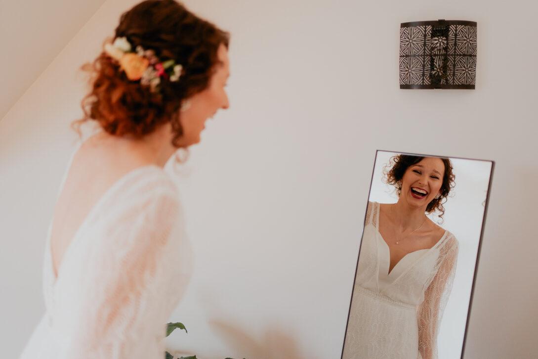roześmiana panna młoda przegląda sie w lustrze wesele w namiocie piotr Czyżewski fotograf na ślub Legionowo