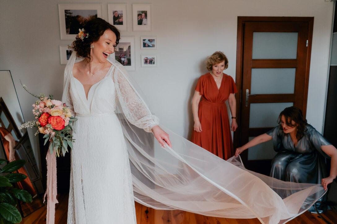 świadkową rozkłada długi welon panny młodej wesele w namiocie piotr Czyżewski fotograf na ślub Legionowo