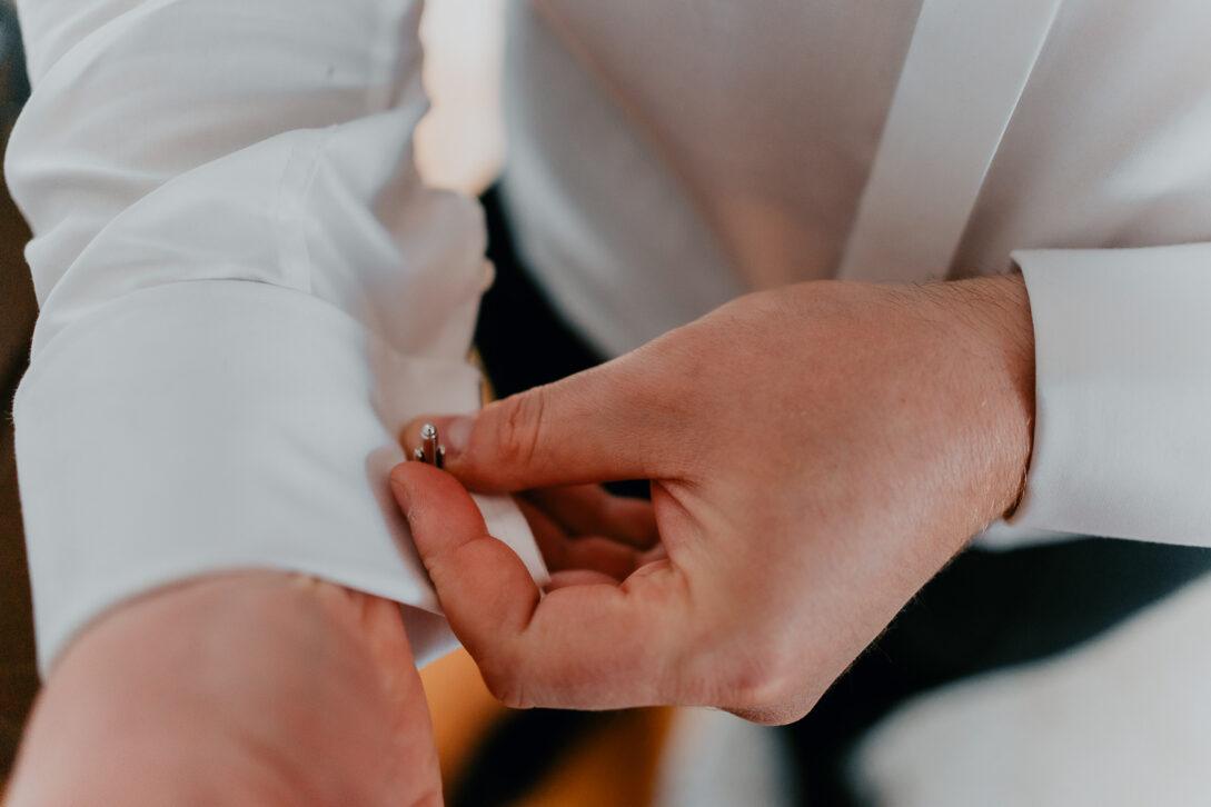 pan młody zapina spinki wesele w namiocie piotr Czyżewski fotograf na ślub Legionowo