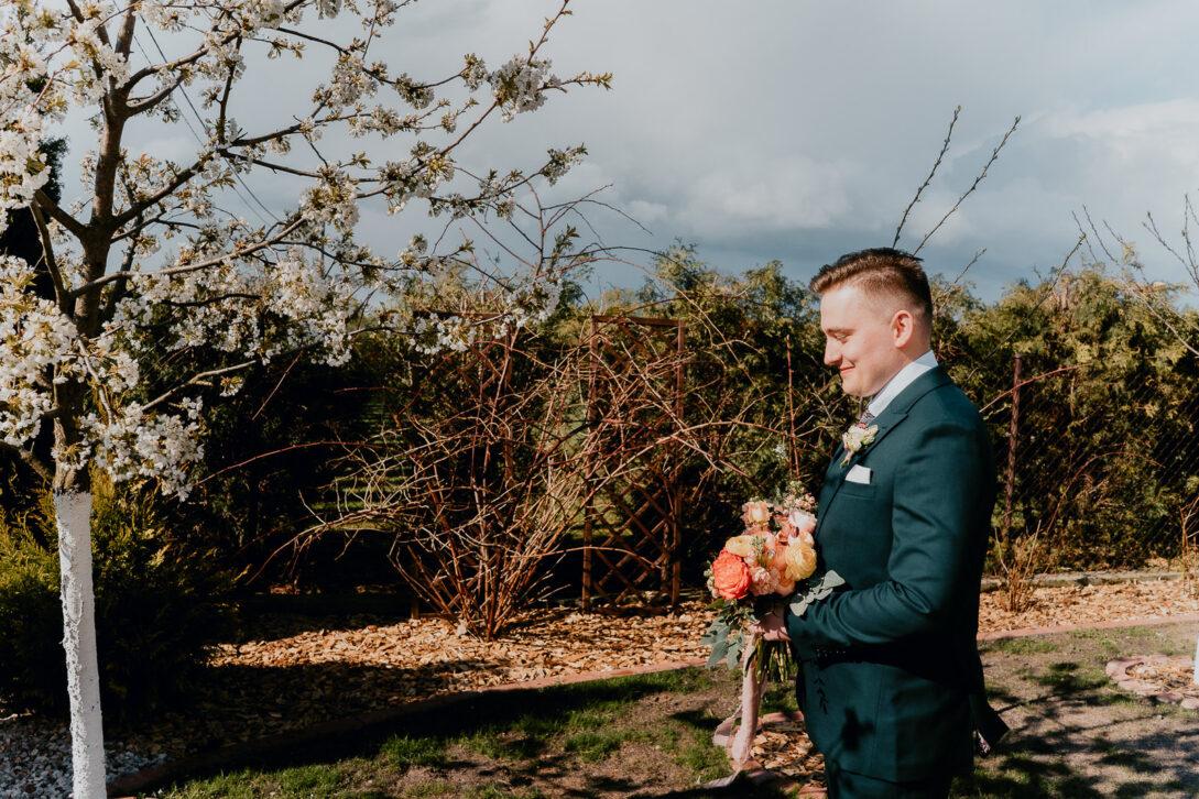 pan młody w ogrodzie z bukietem czeka na pannę młoda wesele w namiocie piotr Czyżewski fotograf na ślub Legionowo