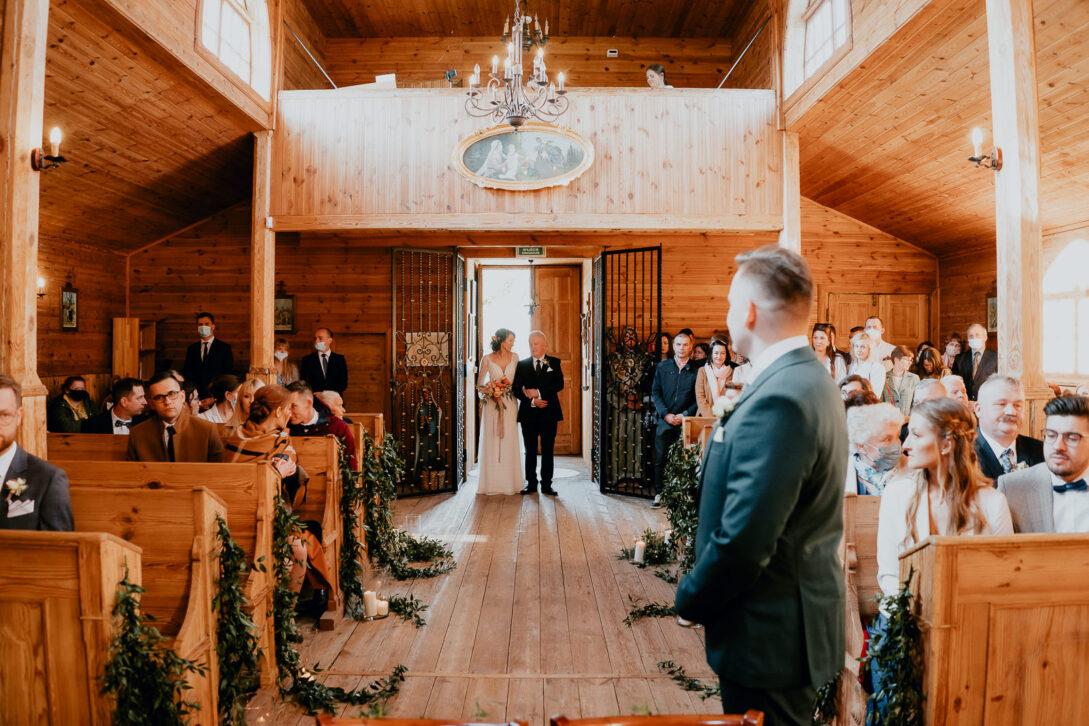 pa młody czeka przed ołtarzem na pannę młoda która prowadzi tata wesele w namiocie piotr Czyżewski fotograf na ślub Legionowo