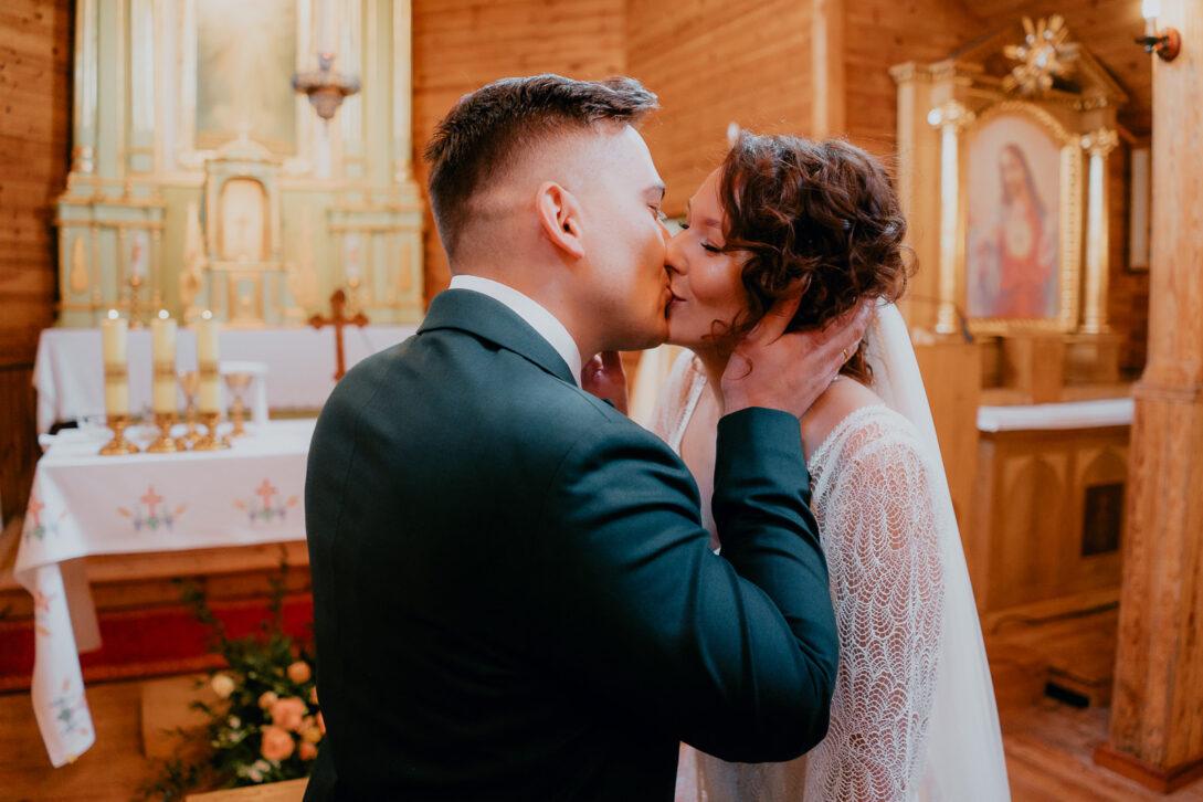 pocałunek pary młodej po zaślubinach w drewnianym kościele wesele w namiocie piotr Czyżewski fotograf na ślub Legionowo