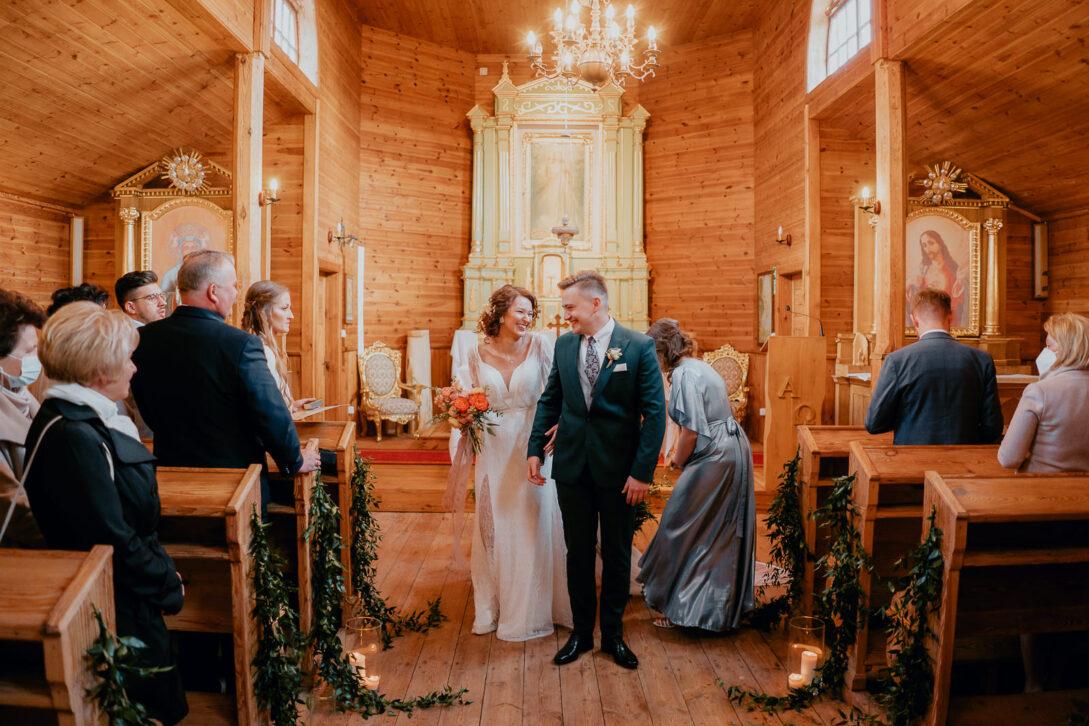 młodzi wychodzą z drewnianego kościoła wesele w namiocie piotr Czyżewski fotograf na ślub Legionowo